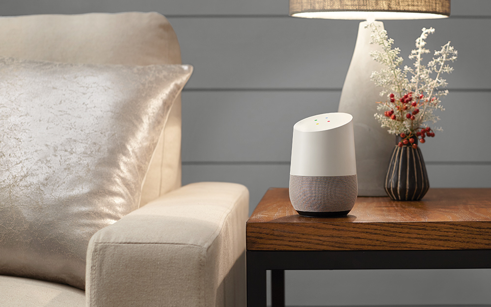 Google Home device on a table in living room.