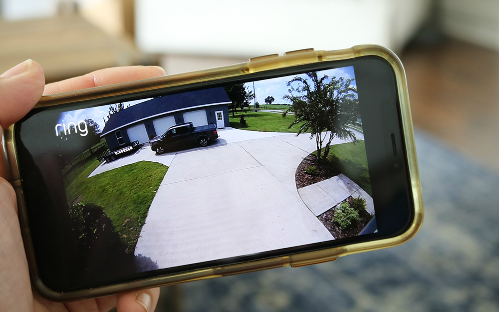 Person watching home security video on a smart phone.