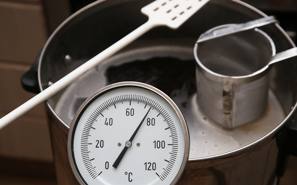 A kettle of homebrew with a thermometer to gauge temperature.