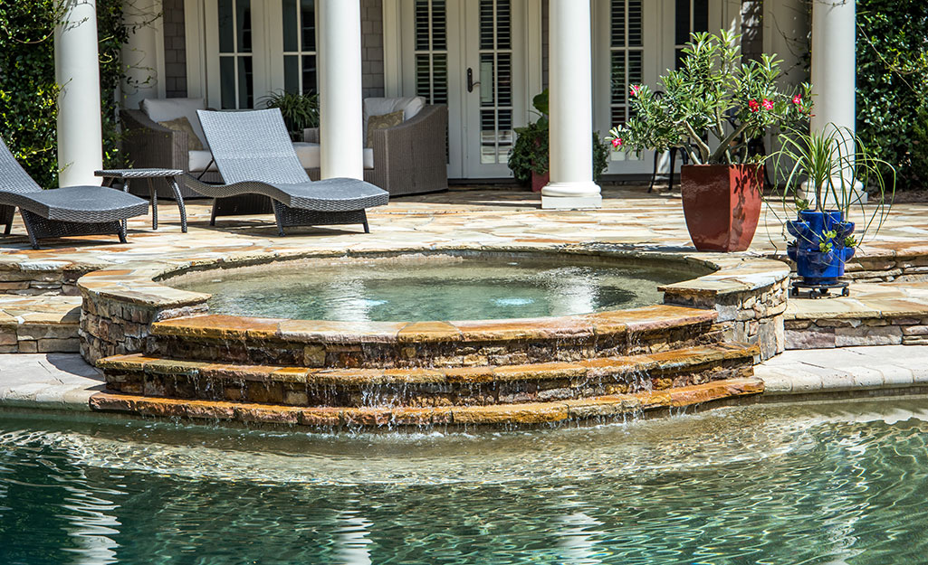 A built-in custom spa with a waterfall feature that feeds into a swimming pool.