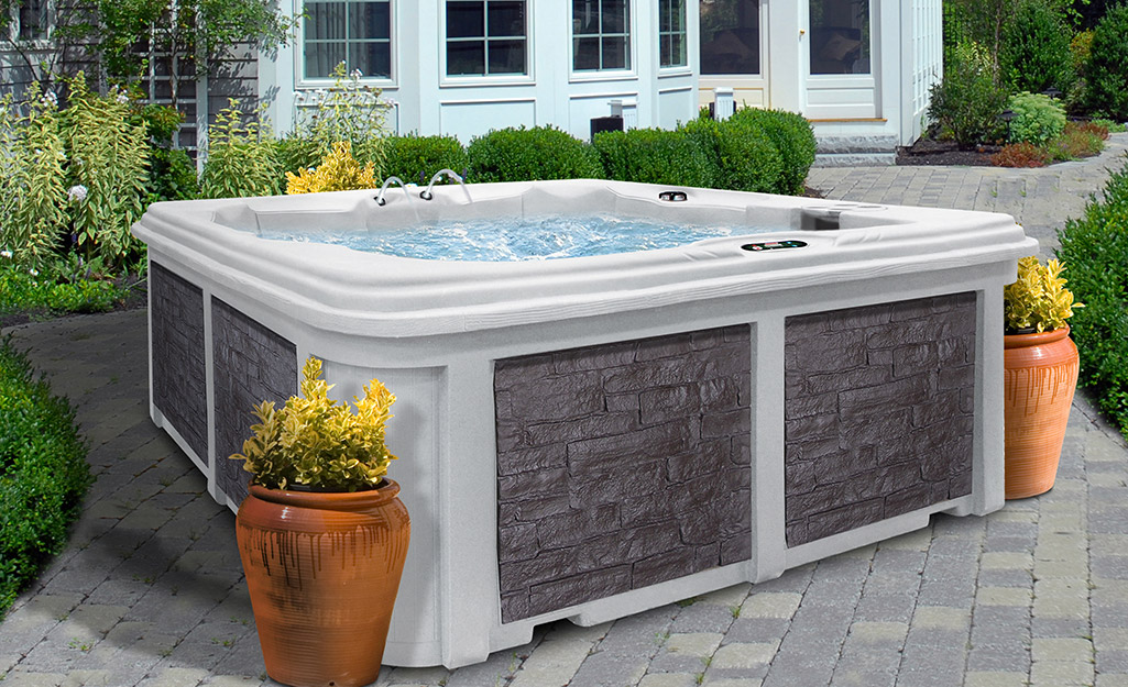 A plug and play hot tub sitting on a brick patio.