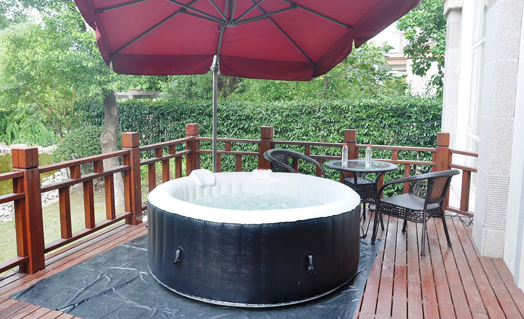 A round, inflatable hot tub placed on a deck.