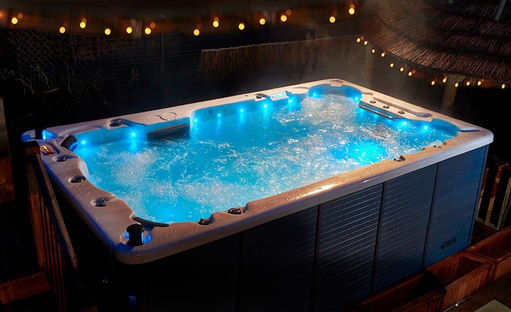 A rectangular swim spa with blue LED lights.
