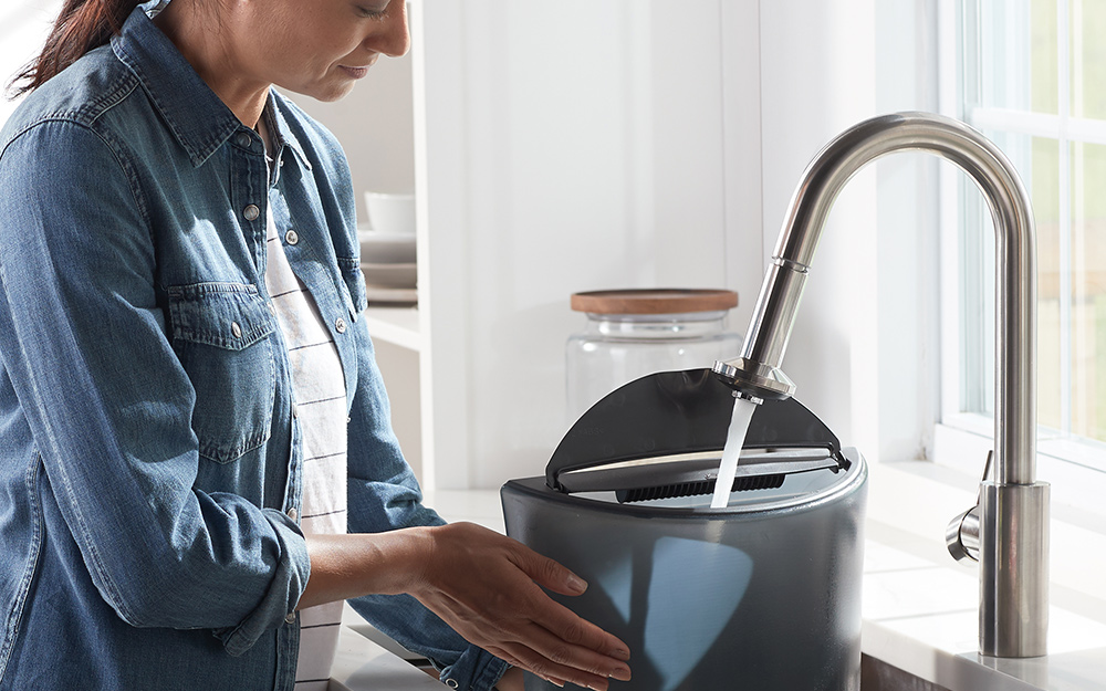 a woman refilling the water in a dehumidifier