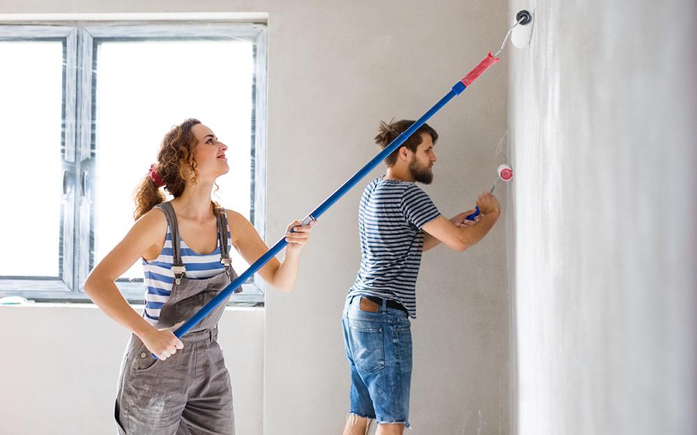 Một người phụ nữ và một người đàn ông đứng bên cửa sổ vẽ một bức tường.