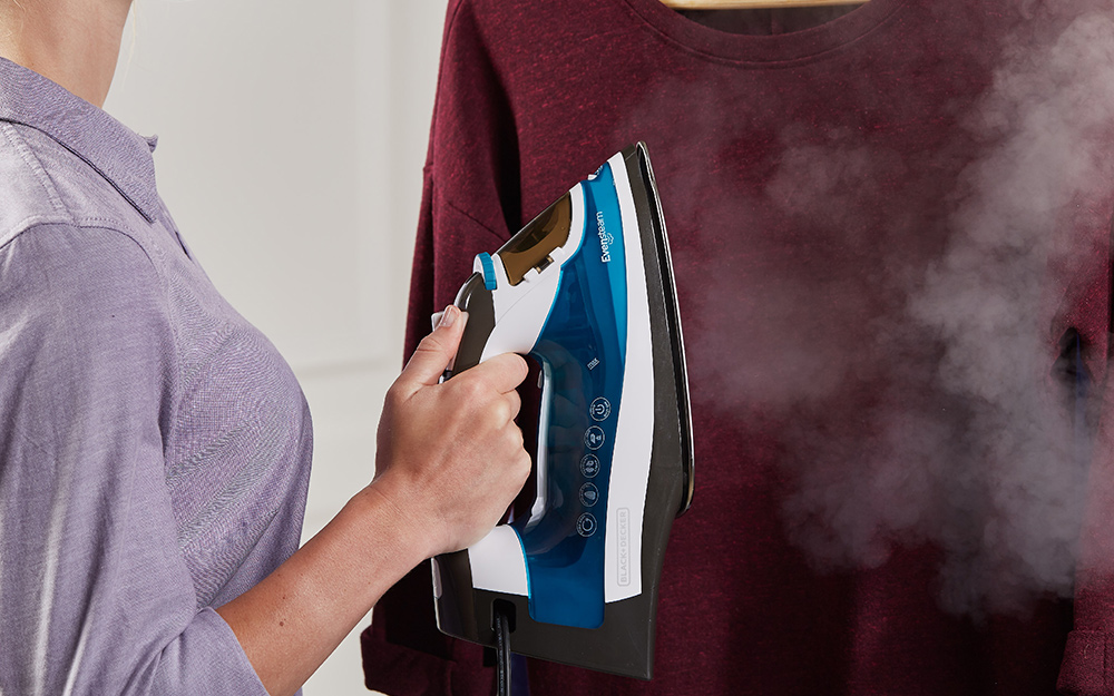 A person using an iron as a steamer.