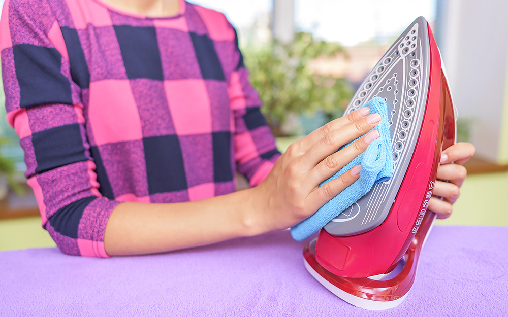 A person cleaning the soleplate of an iron.