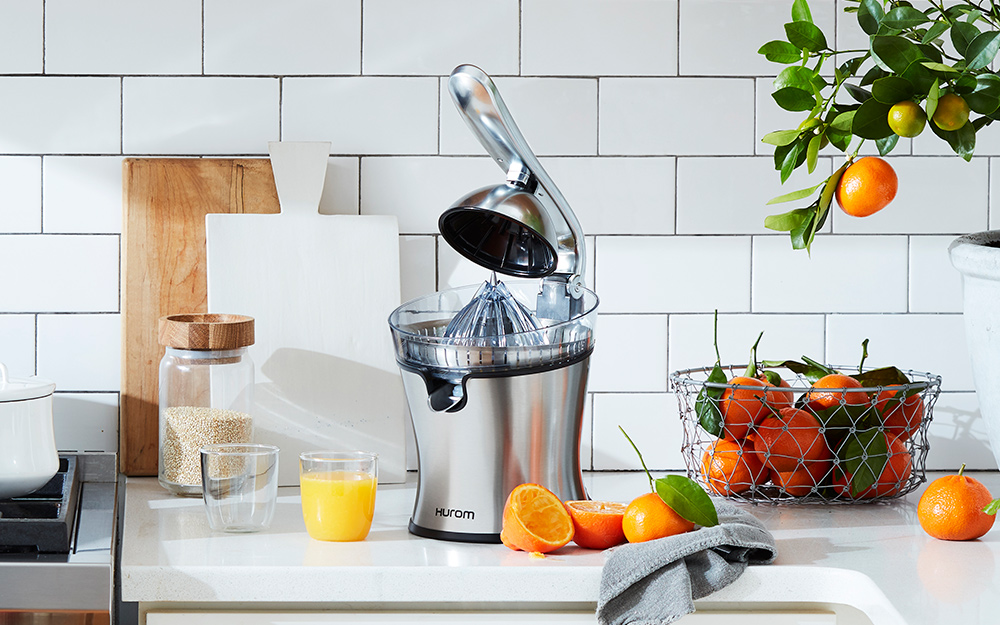 A stainless steel citrus juicer sits on a kitchen counter.