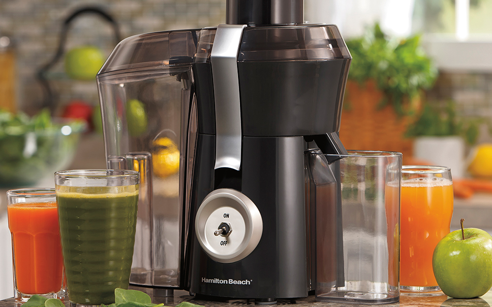 A juice extractor sits in a kitchen next to glasses of different kinds of juice.