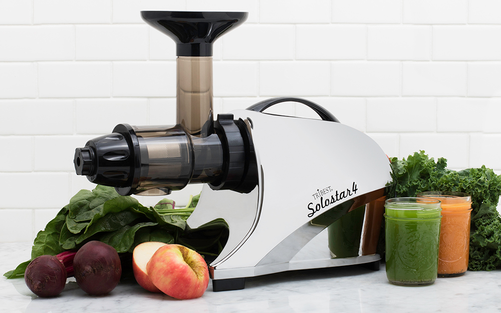 A slow masticating juicer sits on a counter with fruit and vegetables.