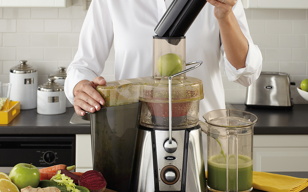 A person loading an apple into a wide mouth juicer.