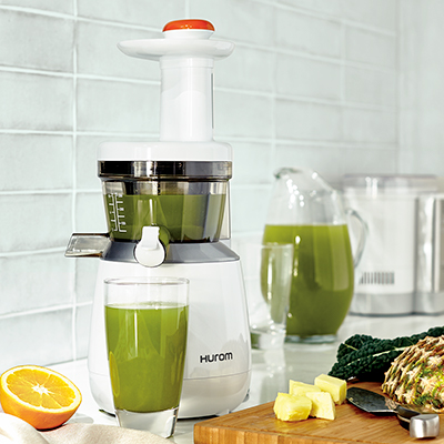 A slow juicer sits on a kitchen counter next to a glass and a pitcher of juice.