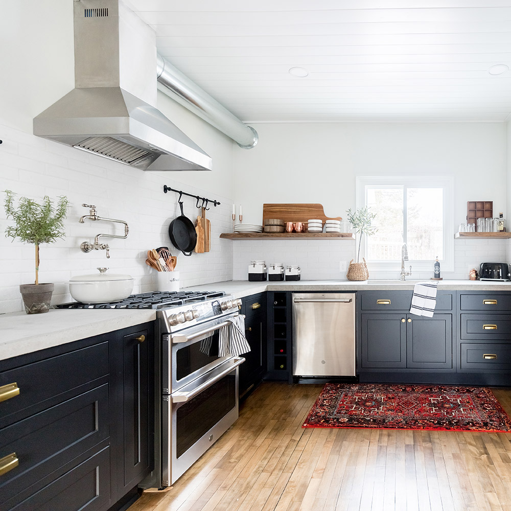 A kitchen with dark lower cabinets and stainless steel appliances.
