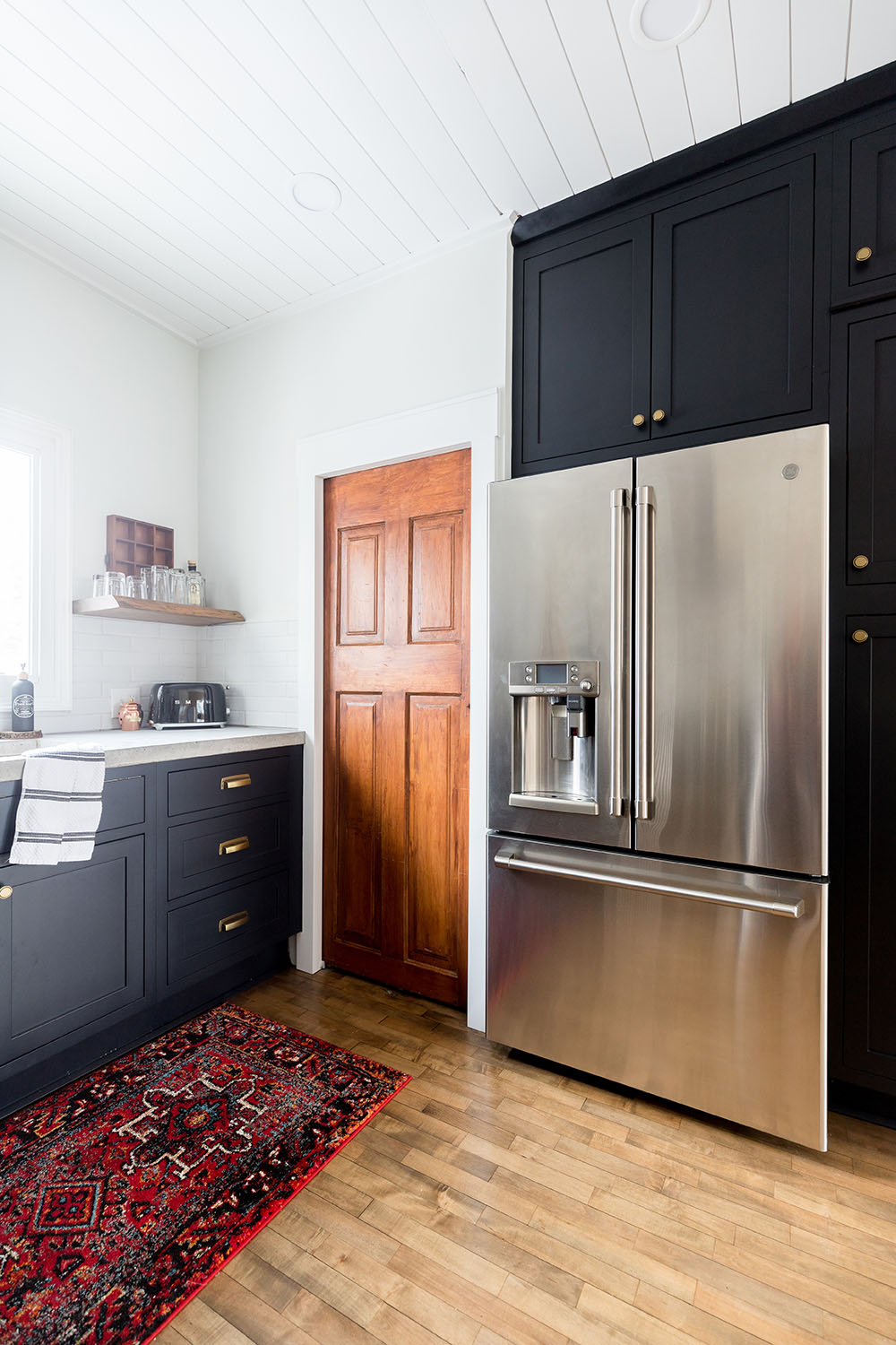 The corner of a kitchen with dark cabinets and a GE Cafe refrigerator.