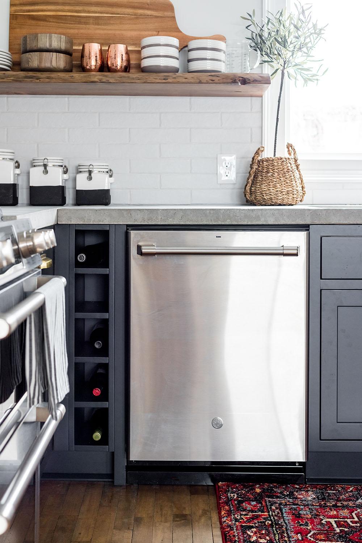 A GE Cafe series dishwasher sitting between dark cabinets.