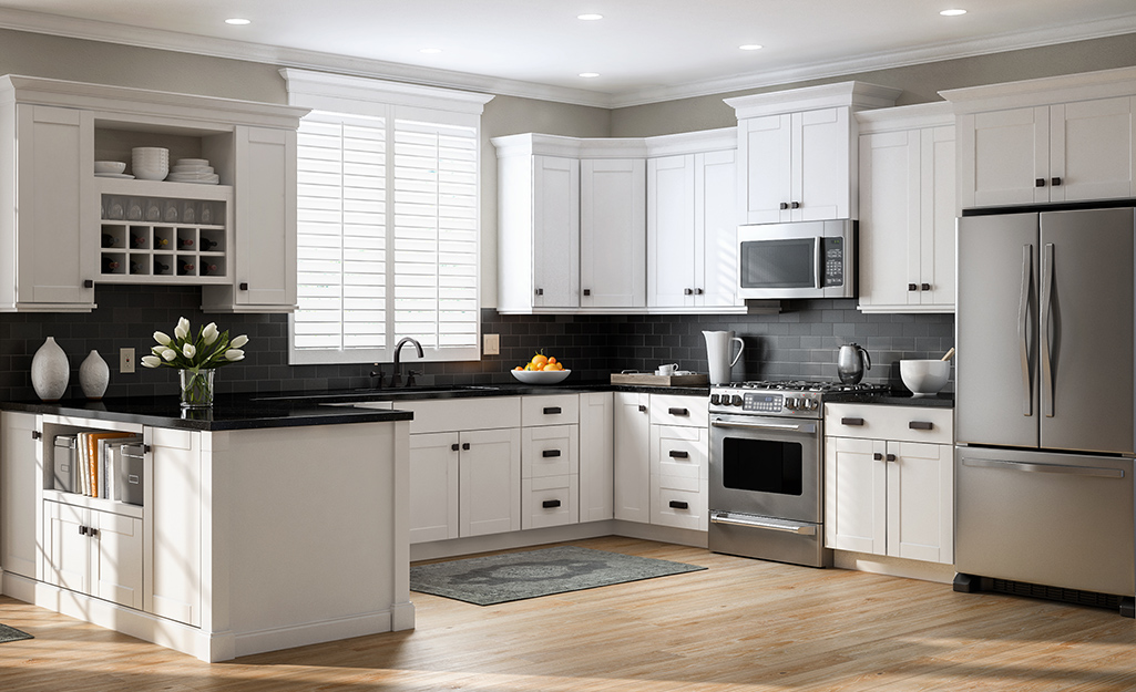 A kitchen with white cabinets and dark hardware.
