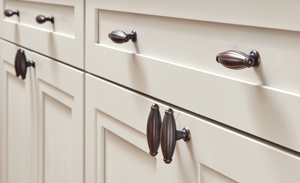Cabinet doors and drawers with dark brass cabinet pulls.