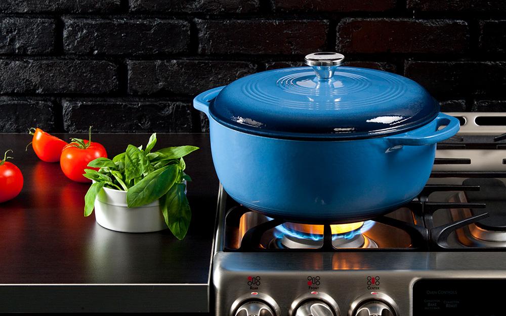 Lò nướng kiểu Hà Lan màu xanh có nắp trên bếp lò.