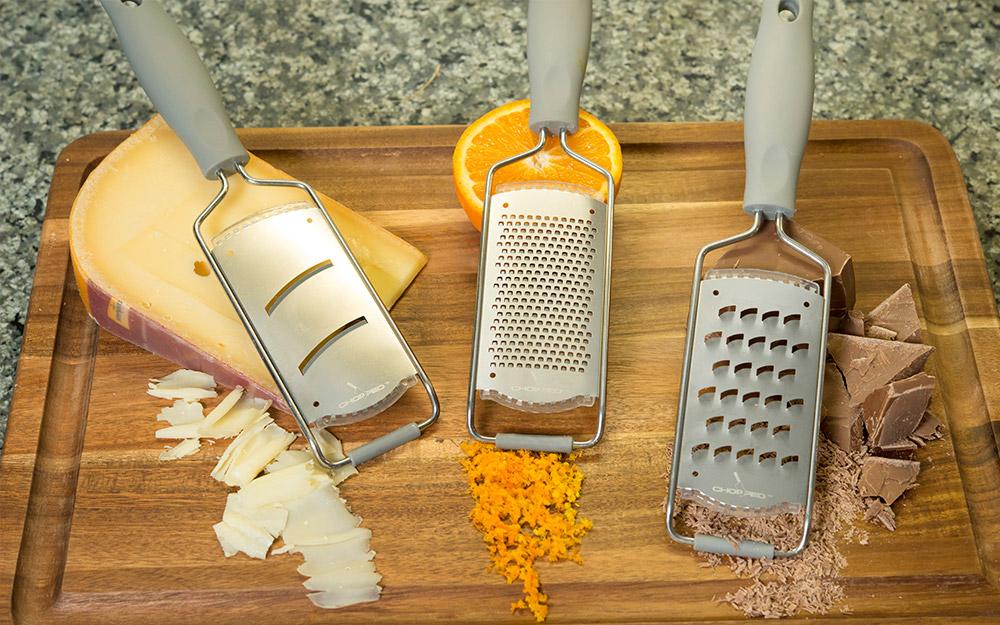 Các loại nạo trên thớt với pho mát bào, miếng sô cô la và vỏ cam cắt nhỏ.
