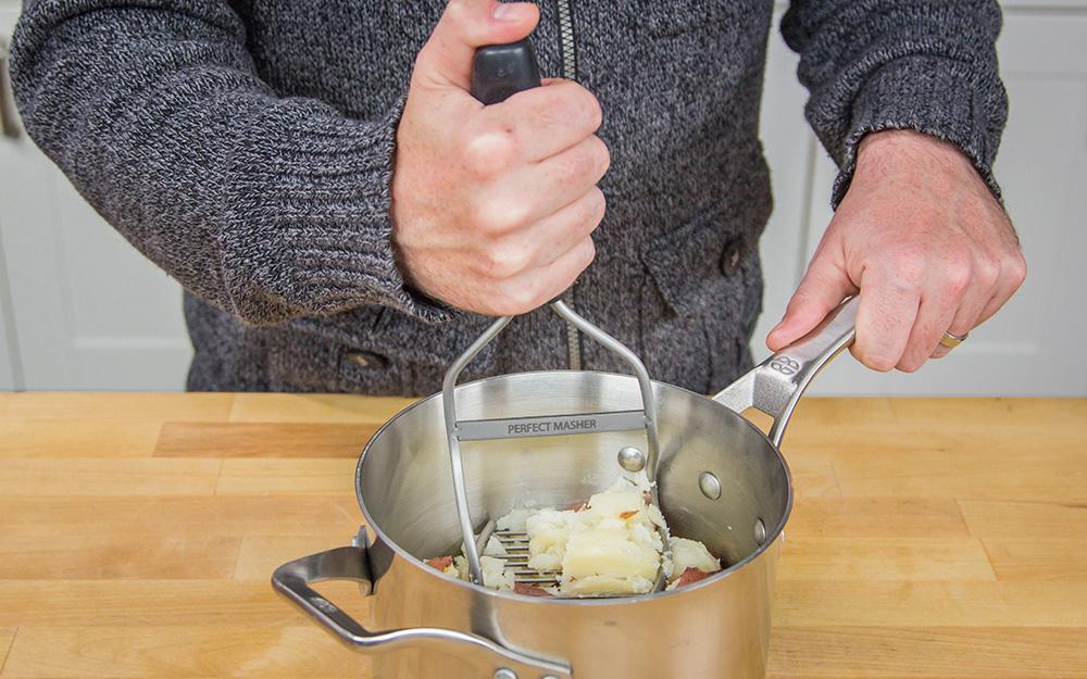 Có người dùng máy nghiền tay để nghiền khoai tây trong bát.