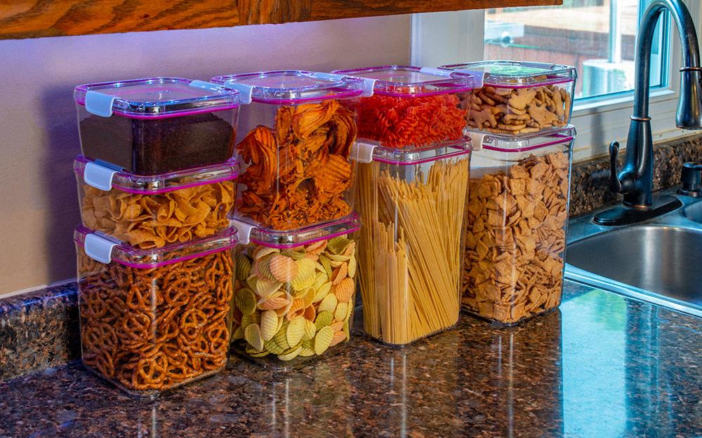 Hộp đựng thực phẩm có kích thước và hình dạng khác nhau, chứa đầy bánh quy và các loại thực phẩm khác, trên quầy bếp.