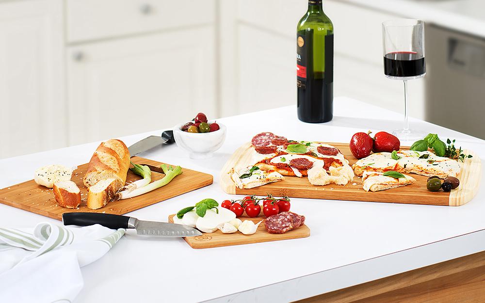 Bánh mì cắt lát, pho mát và các loại thực phẩm khác trên thớt trên kệ bếp.