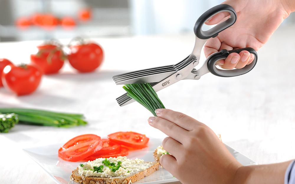Ai đó đang dùng kéo để cắt thức ăn trong nhà bếp.