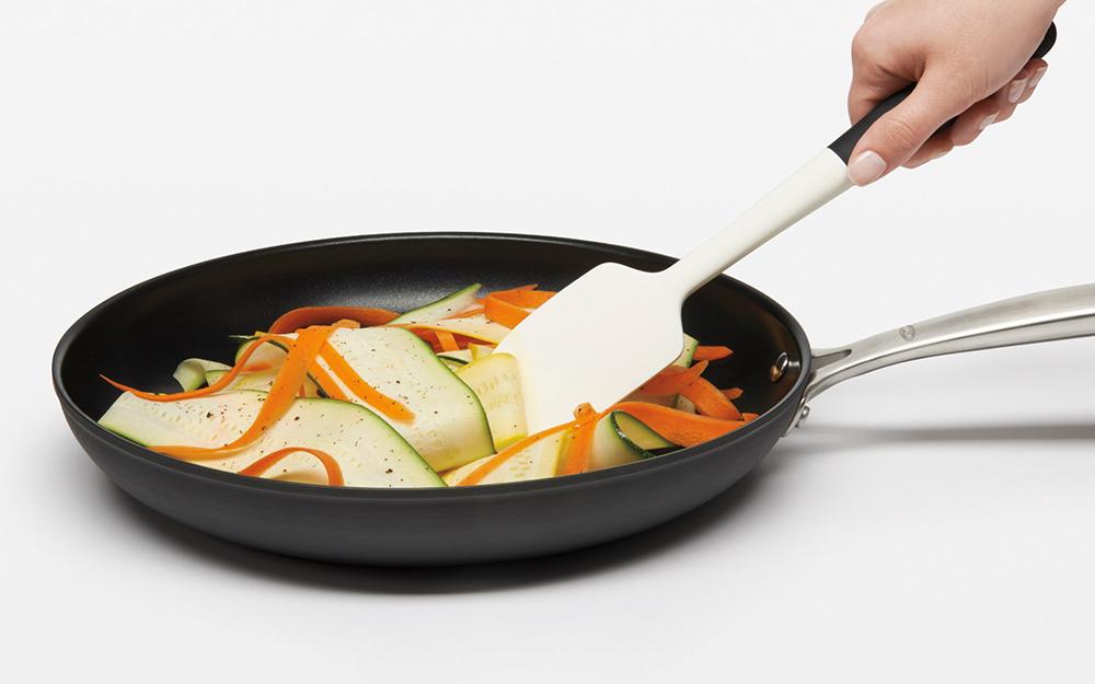 Có người dùng thìa ni lông để đảo thức ăn trong chảo.