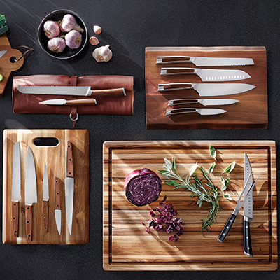 An array on kitchen knives resting supported by planks cutting boards.