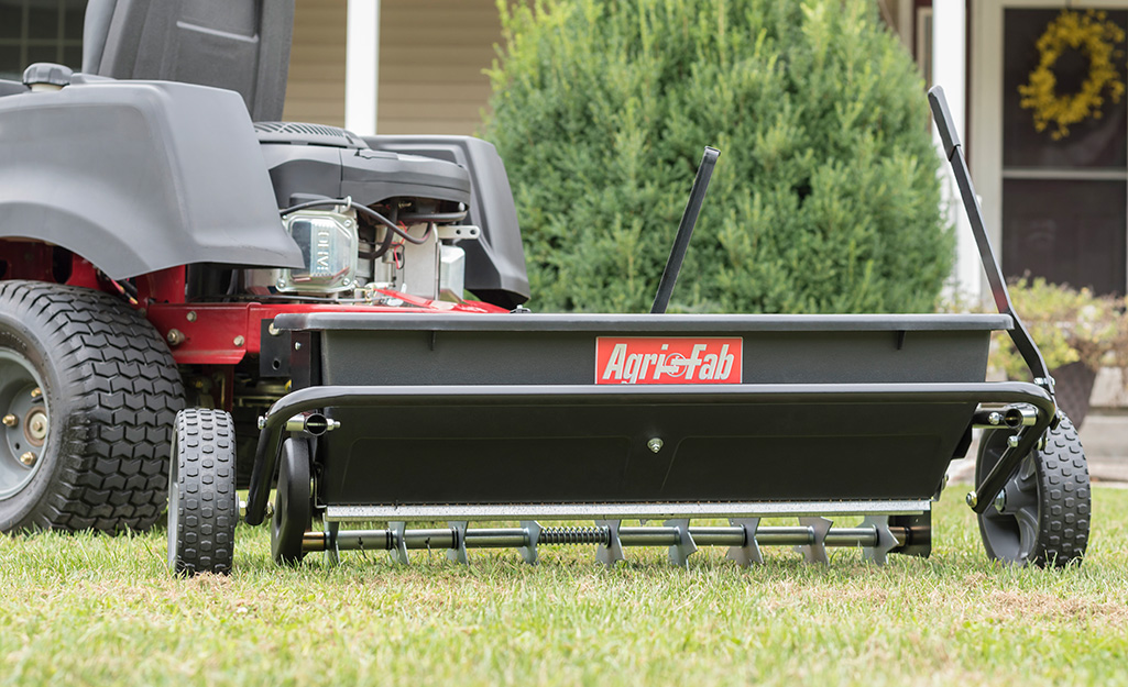 A garden tractor pulling a spiker seed drop spreader over a lawn.