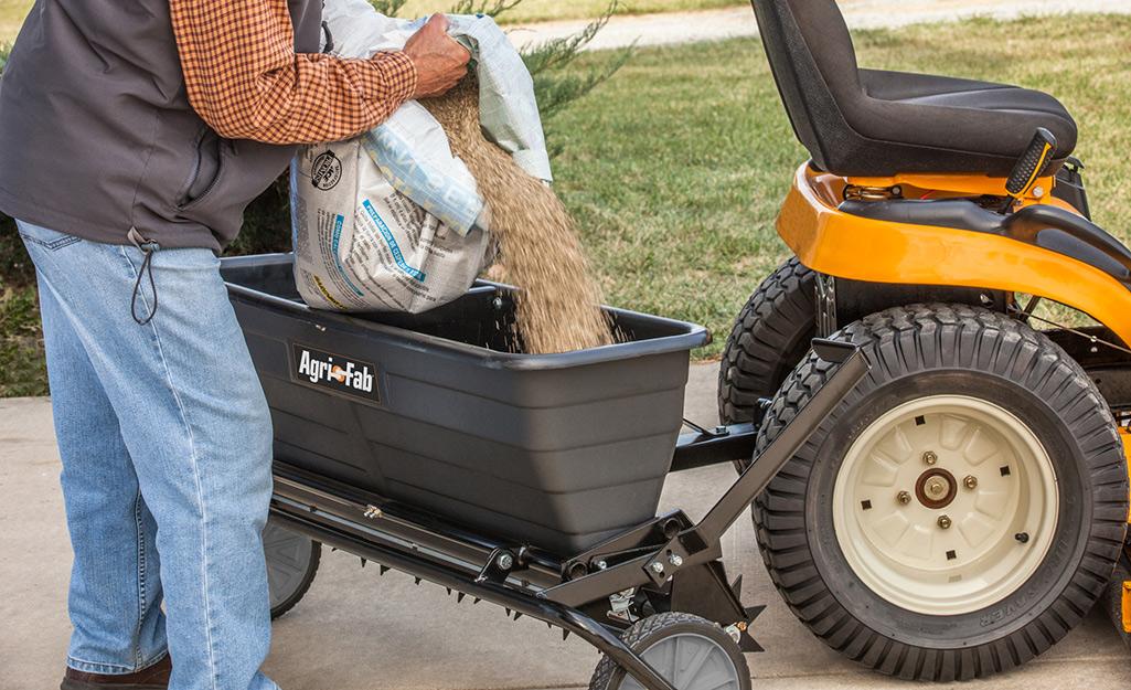Someone filling a fertilizer spreader over a driveway.