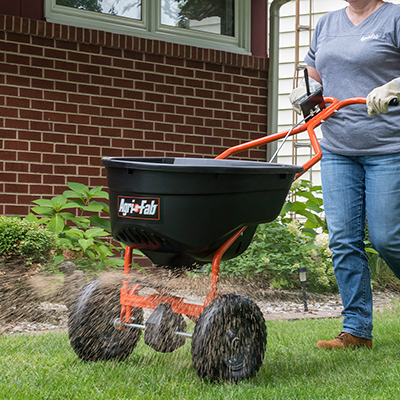 A woman wearing gardening gloves pushing a lawn spreader over the grass.