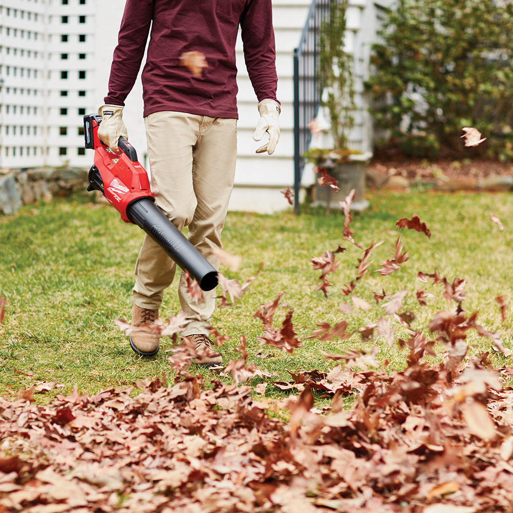A person uses a leaf blower in their yard.