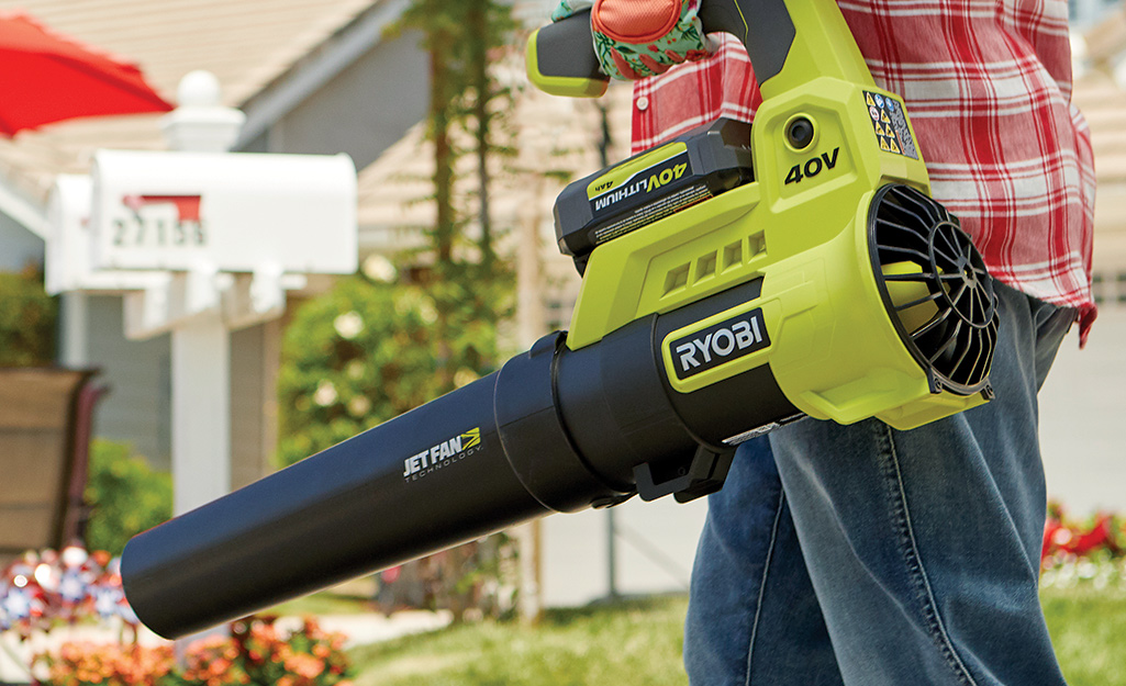 A person carries a leaf blower with a custom handle.