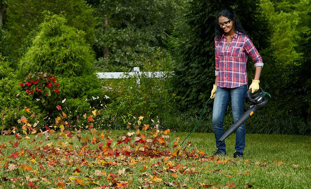 A woman using a leaf blower to clean up leaves.