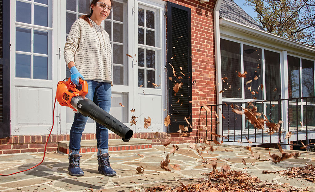 A person uses a corded leaf blower to clear leaves from a patio.