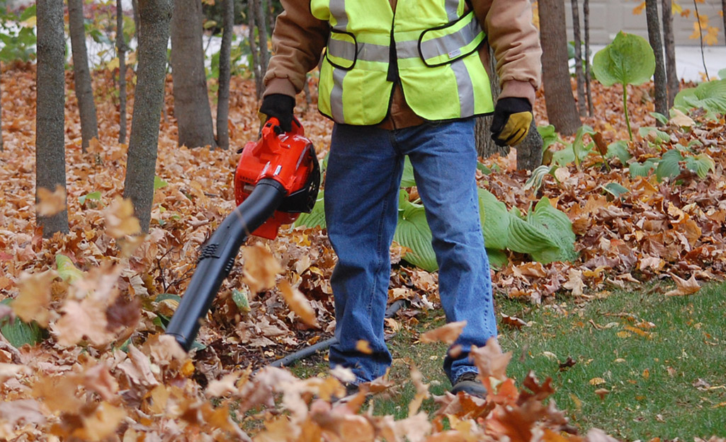 A worker uses a cordless blower on leaves.