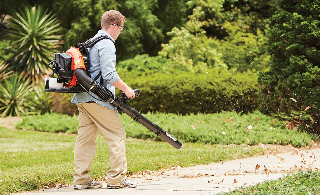 A person uses a backpack-style leaf blower.