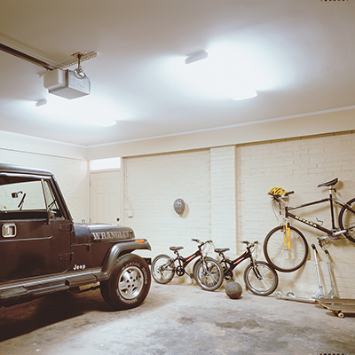Bright overhead garage lighting featured in a garage with a car and bicycles.