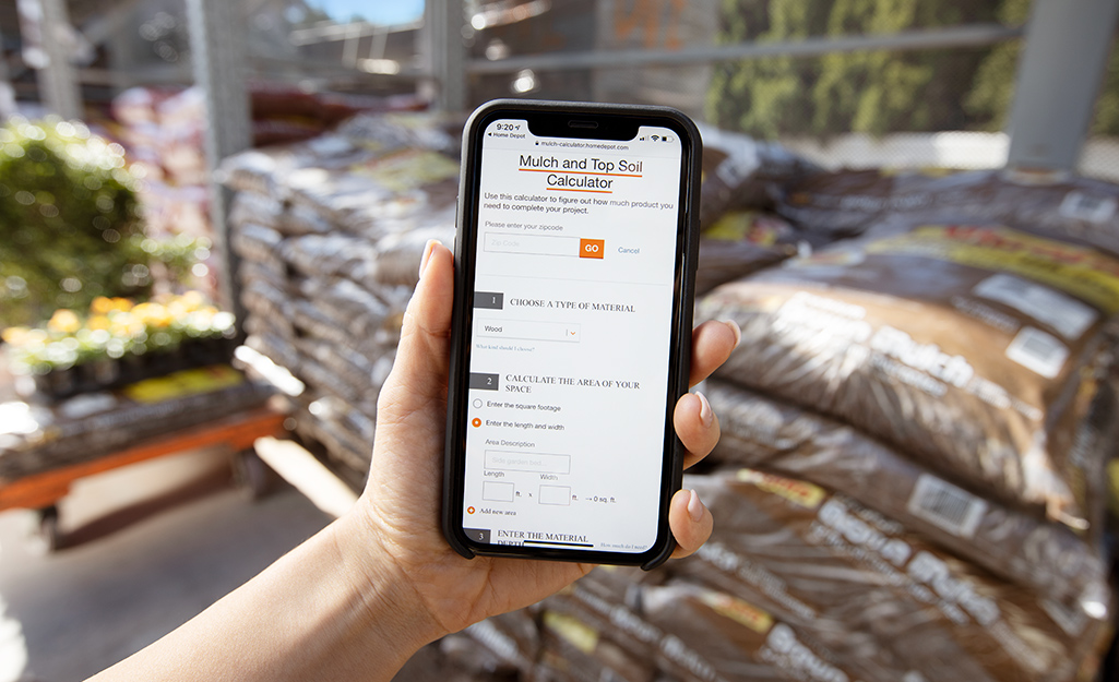 A person holds up a smartphone with The Home Depot mulch calculator on the screen.