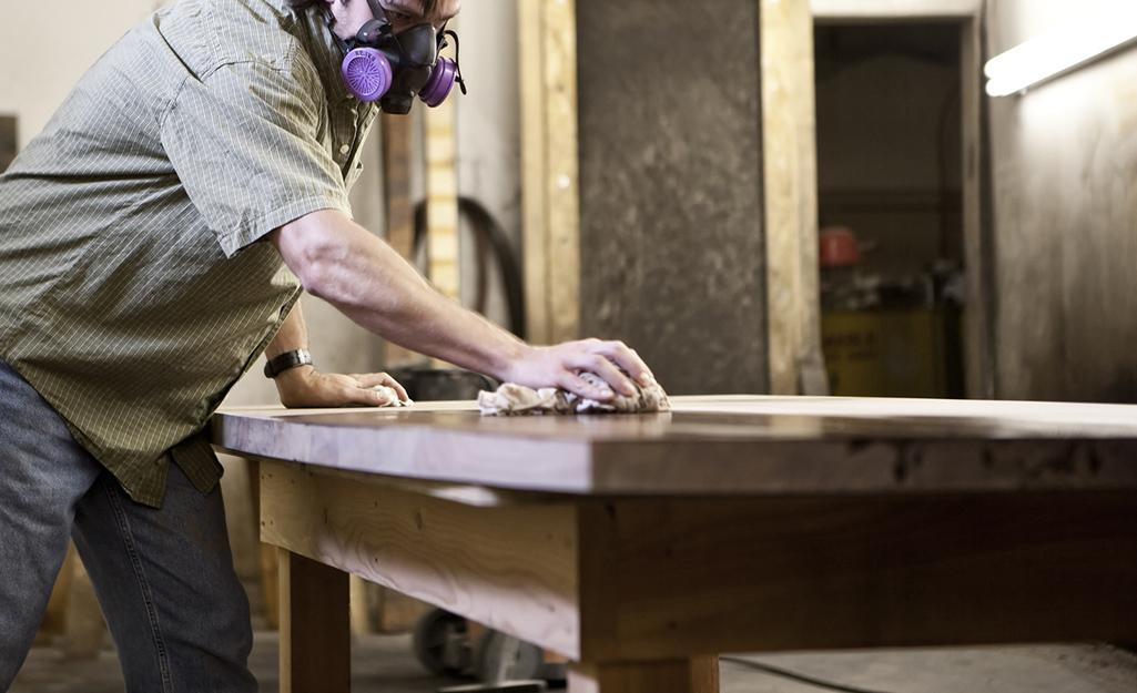 Một người dùng giẻ bôi vết bẩn lên bàn gỗ.