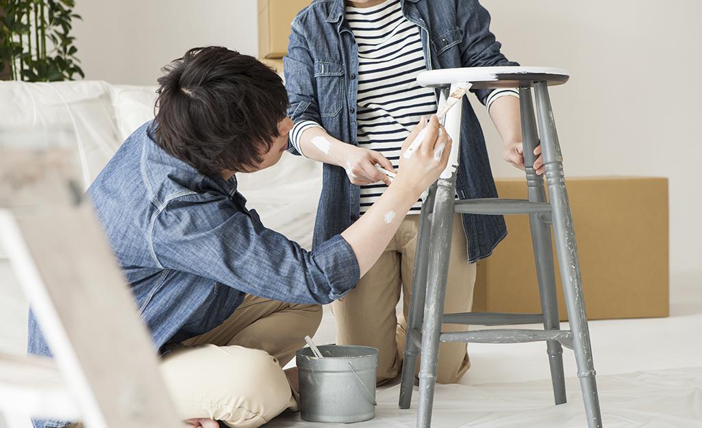 Hai người vẽ một chiếc ghế đẩu bằng cọ sơn.