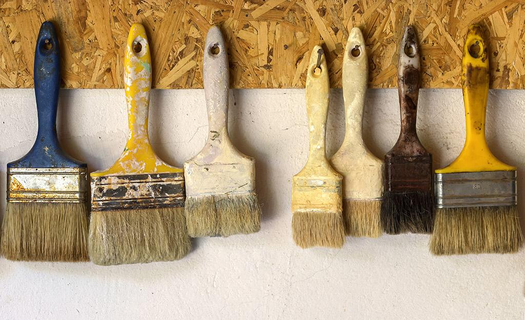 Chổi sơn treo trên móc để lưu trữ trên tường.