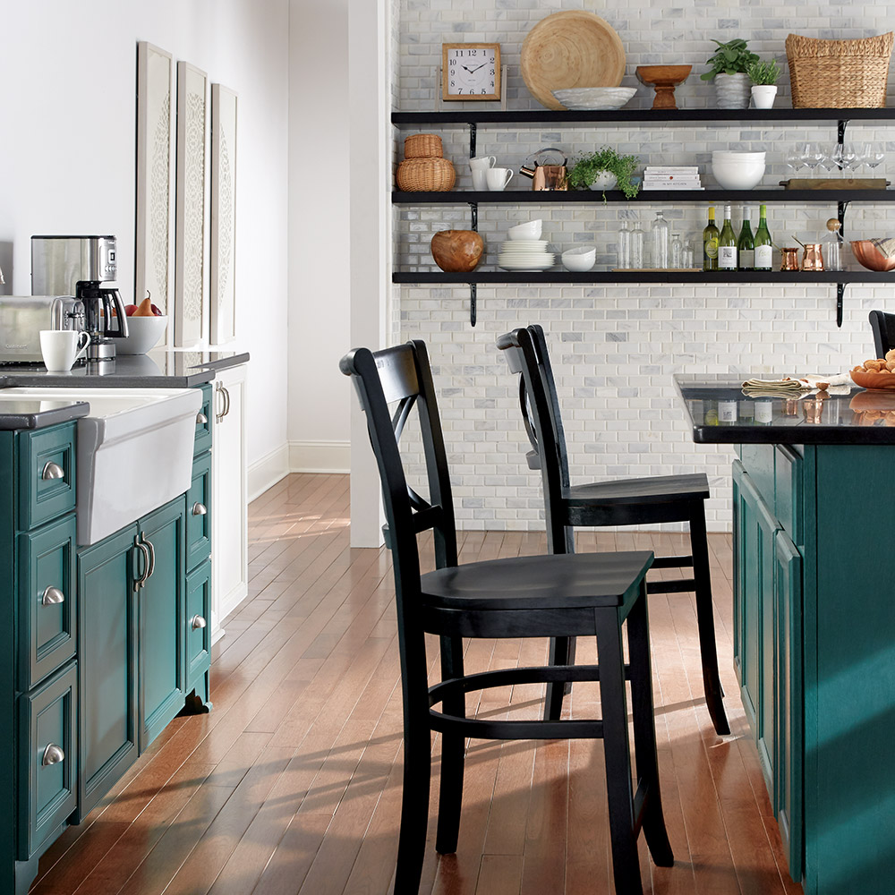 Farmhouse-style kitchen cabinets painted in a green tone.