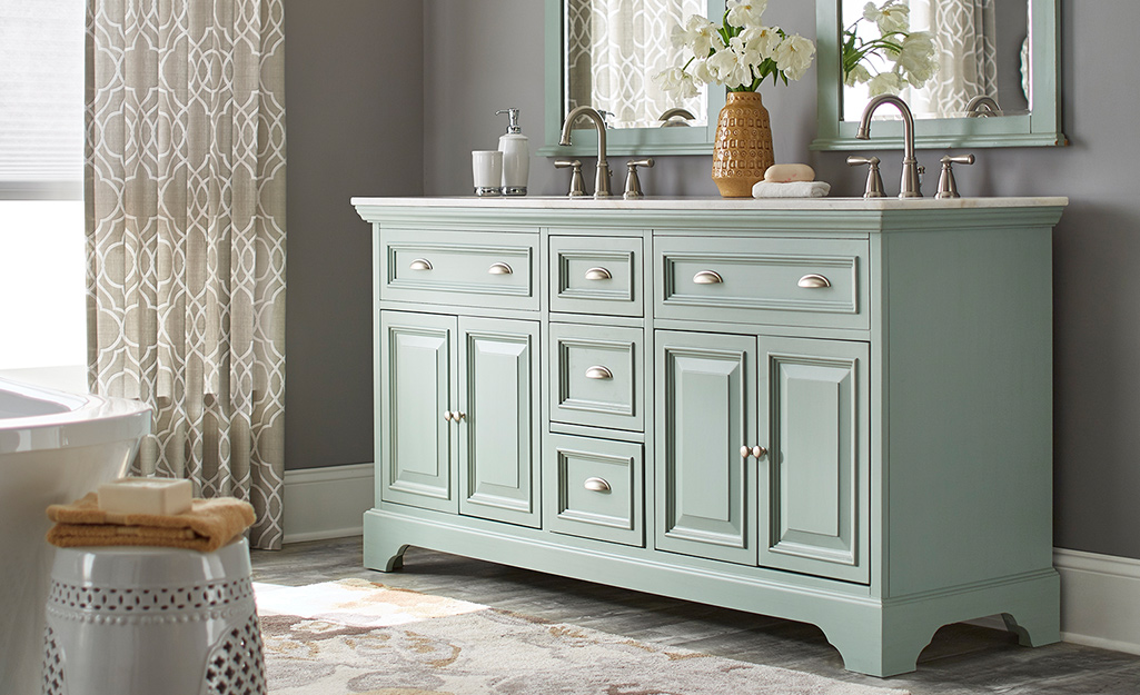 Bath cabinet painted in a light green shade.