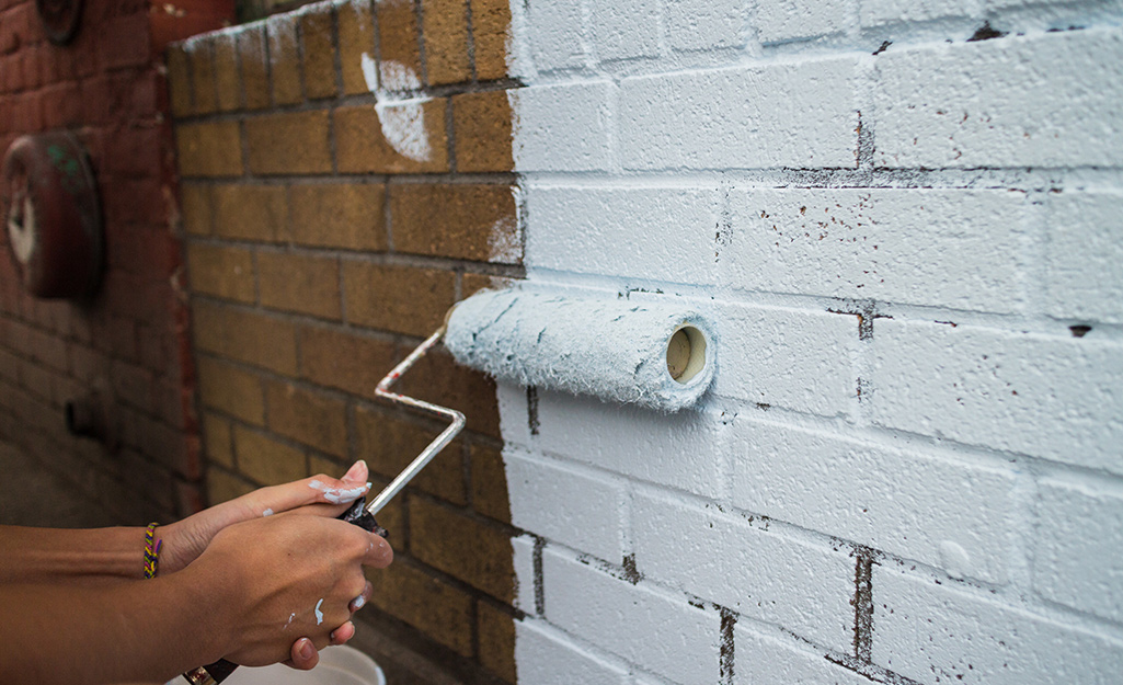 A person paints a brick wall with a rough surface roller cover.