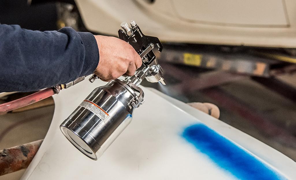 Một người sử dụng máy phun sơn bằng khí nén.