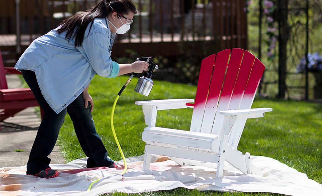 Một người phụ nữ sử dụng máy phun sơn để sơn một chiếc ghế Adirondack.