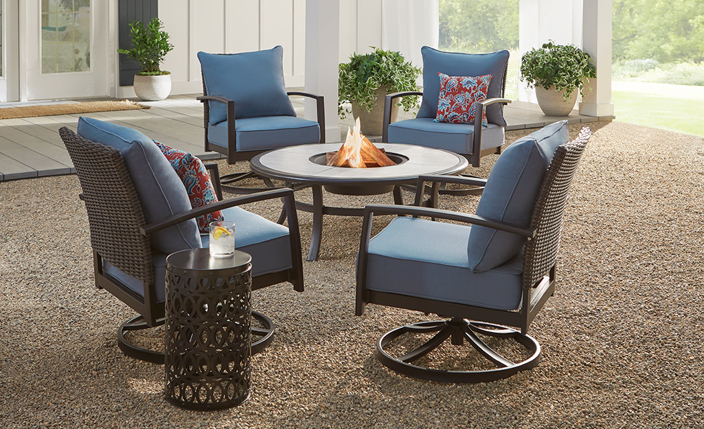 Black patio furniture with blue cushions on a patio.