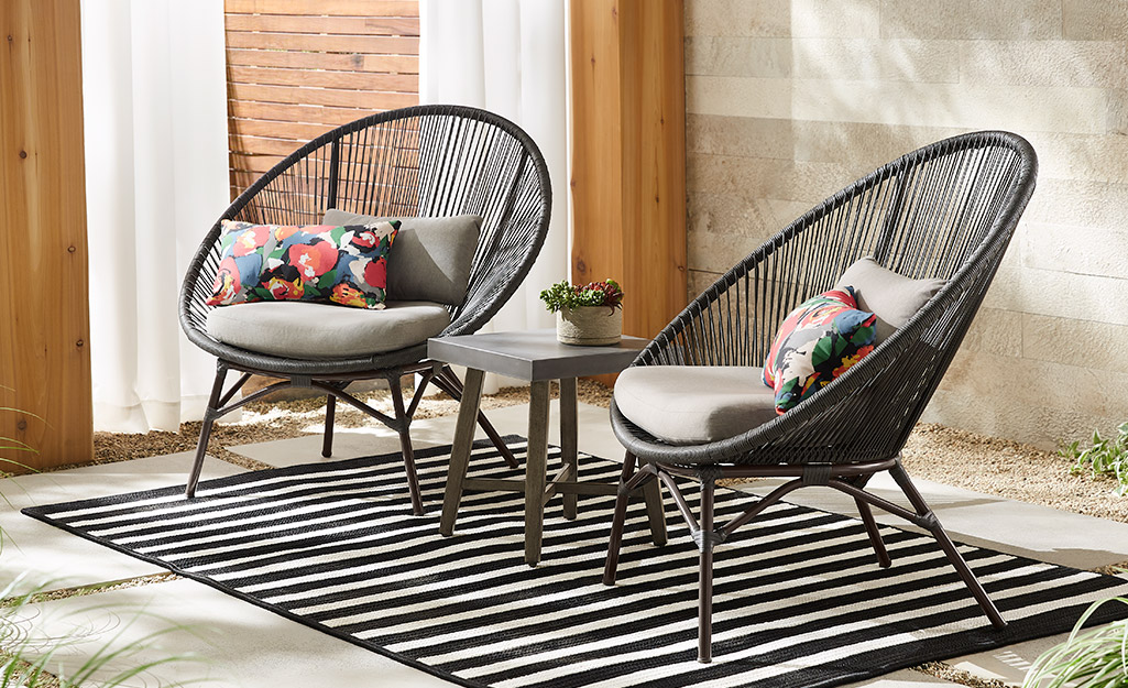 Two chairs and a side table with a black and white rug on a patio.